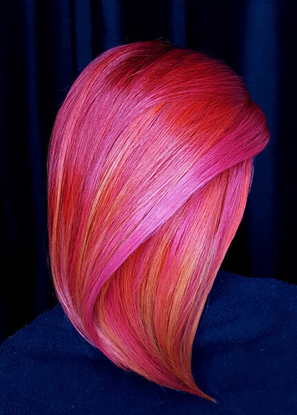 Model showing vibrant pink hair with touches of yellow