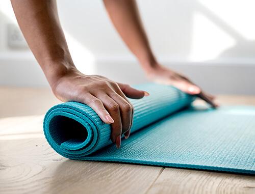 Women's hands on yoga mat