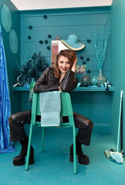 Hairstylist Larisa Love sitting on blue chair smiling