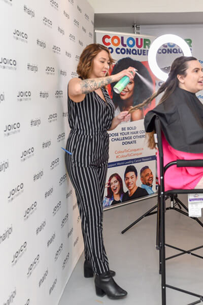 Hairstylist doing models hair at event