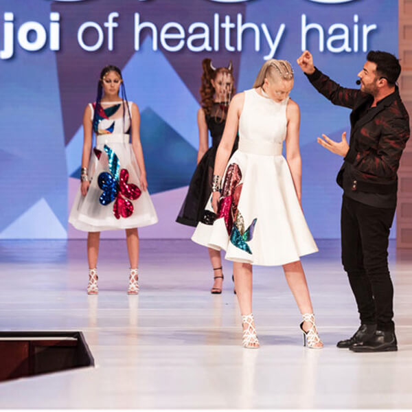 Richard Mannah on stage with model showing her hairstyle