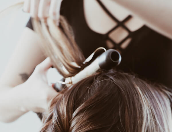 Stylist curling clients hair