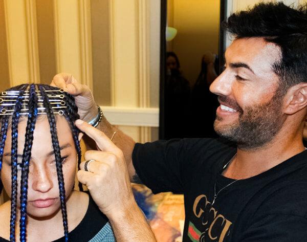 Hair stylist Richard Mannah styling models hair at hair show