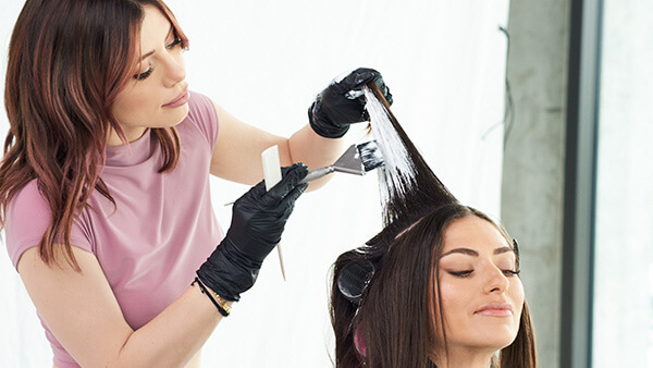 Hair Stylist Larisa Love coloring models hair with professional hair color