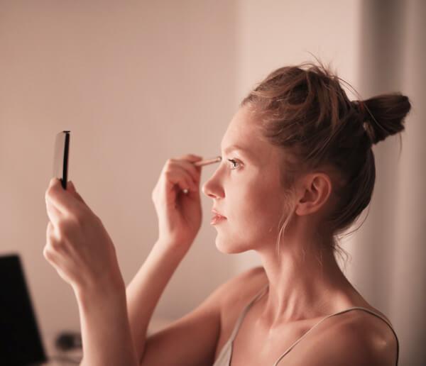 Women putting on eye makeup in mirror