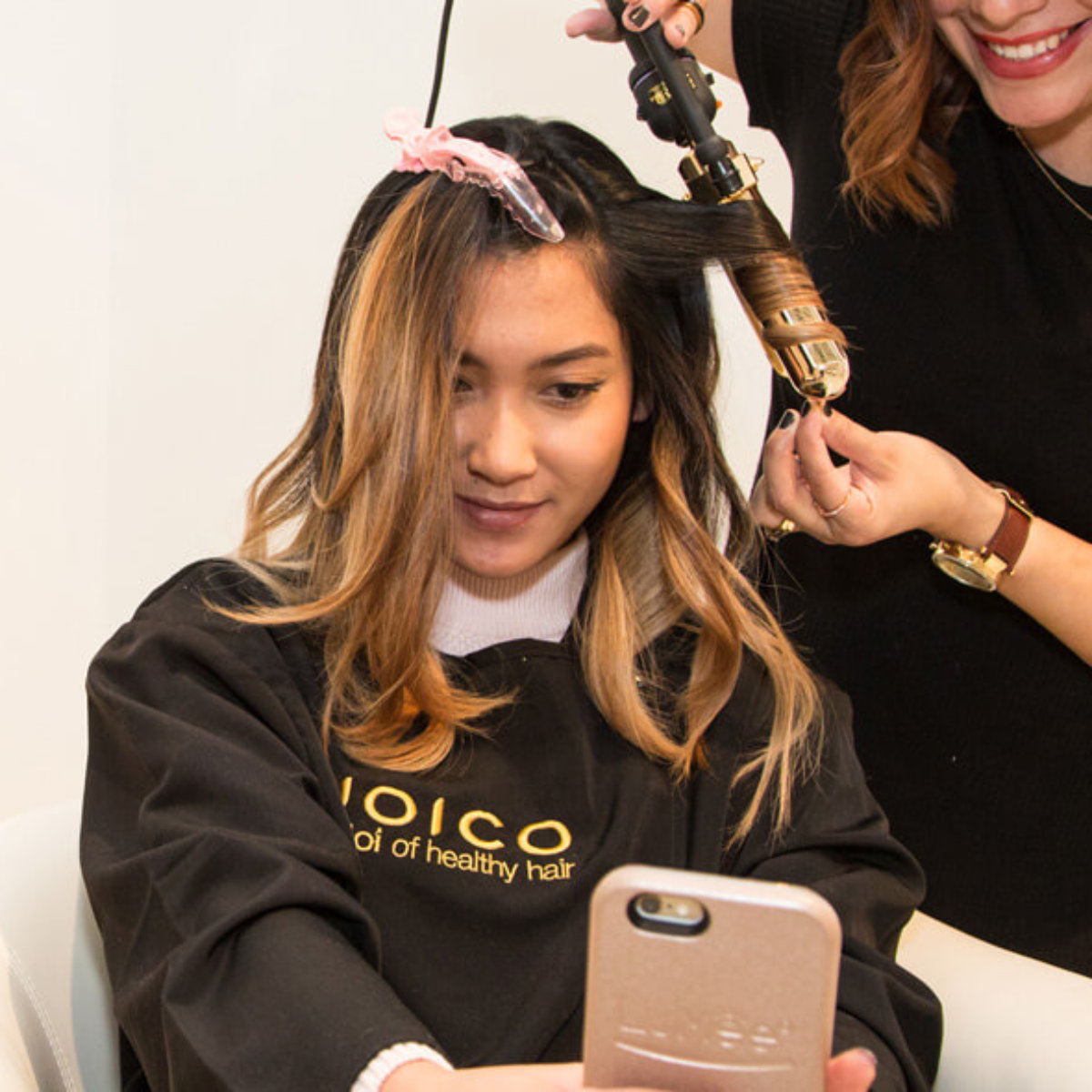 Womens hair being curled by a hairstylist