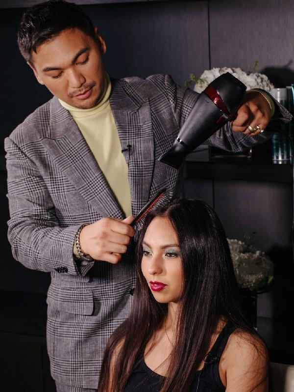 Hair stylist blow drying womens hair