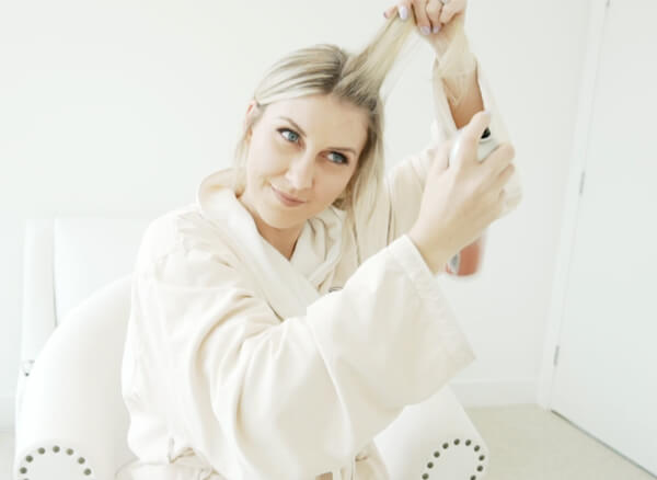 Women spraying hair with Dry shampoo
