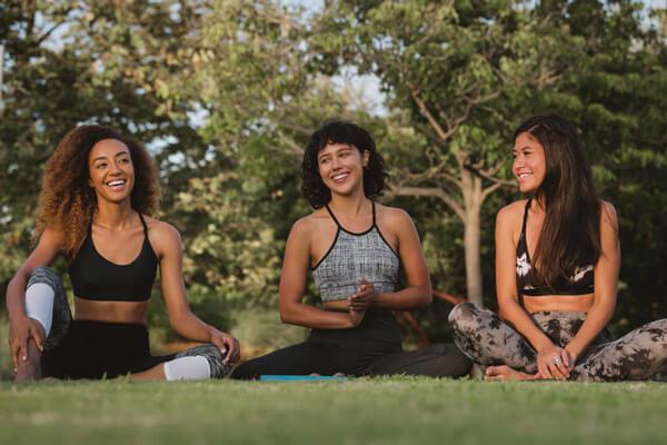 Three women doing yoga in park