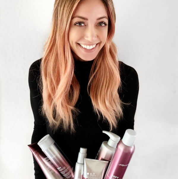 Hairstylist Jill Buck holding Defy Damage products