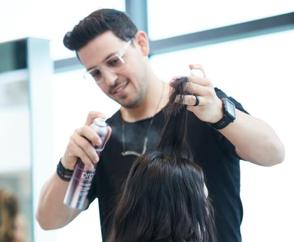 Stylist Ricardo Santiago prepping clients hair