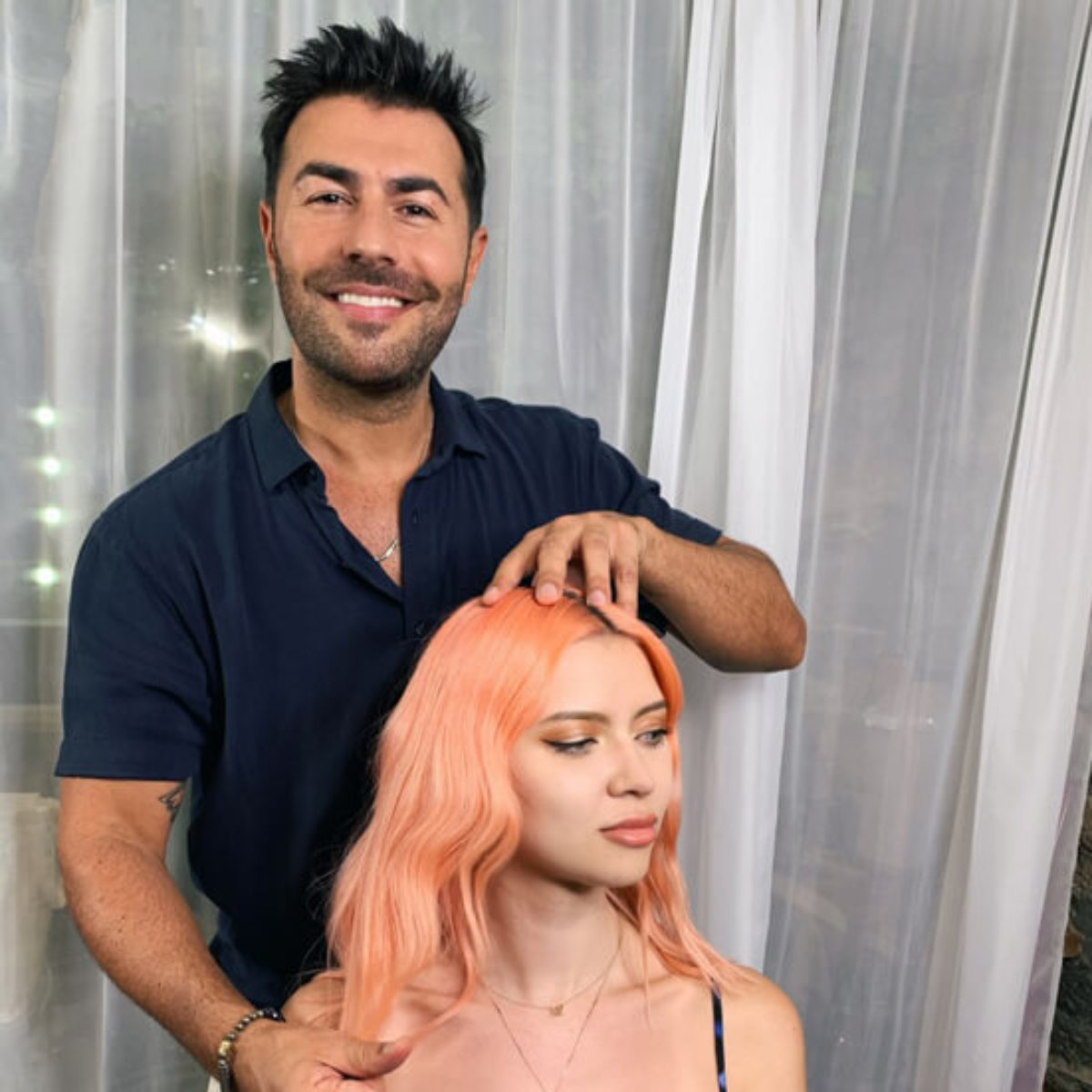 Stylist Richard Mannah showing models hair curled