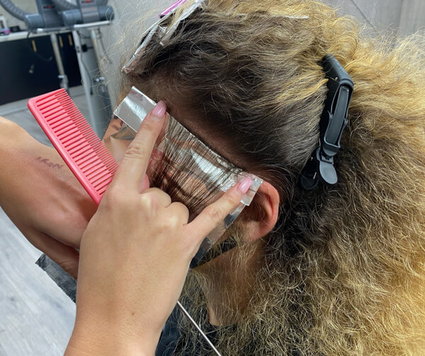 Women getting hair colored with foils