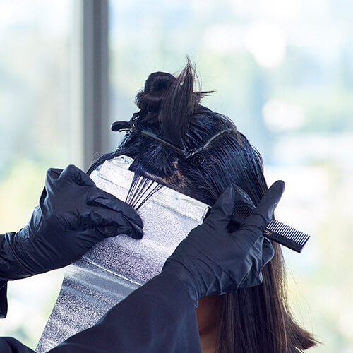 Client getting hair colored with foils