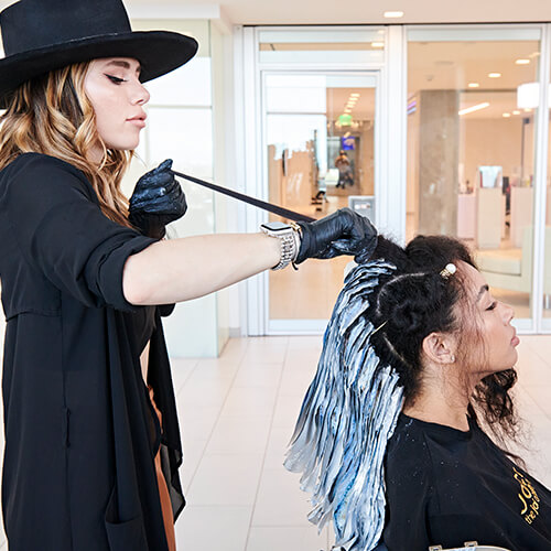 Hairdresser coloring womans hair in salon