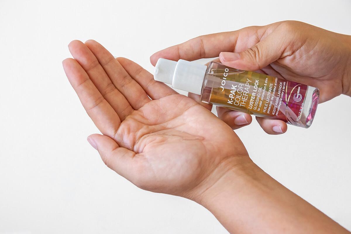 Joico K-pak glossing oil bottle by hand